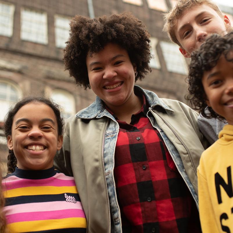 Groepje kinderen kijkt lachend de camera in